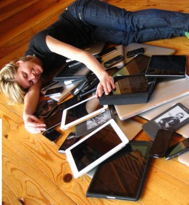 lying with numerous tech devices